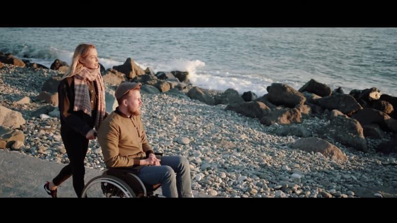 Un soignant poussant quelqu'un dans un fauteuil roulant.