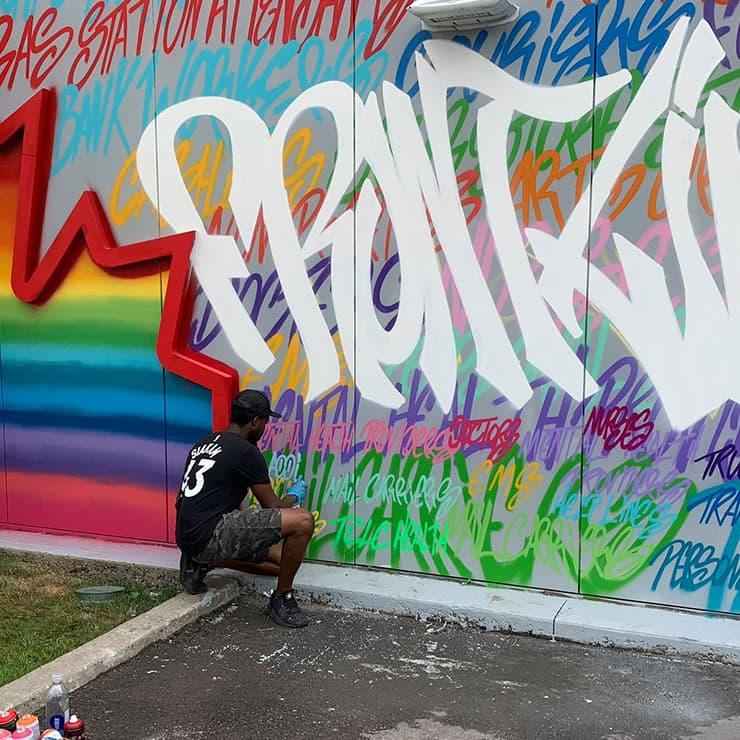 L'artiste Jessey Pacho devant une murale à Petro-Canada