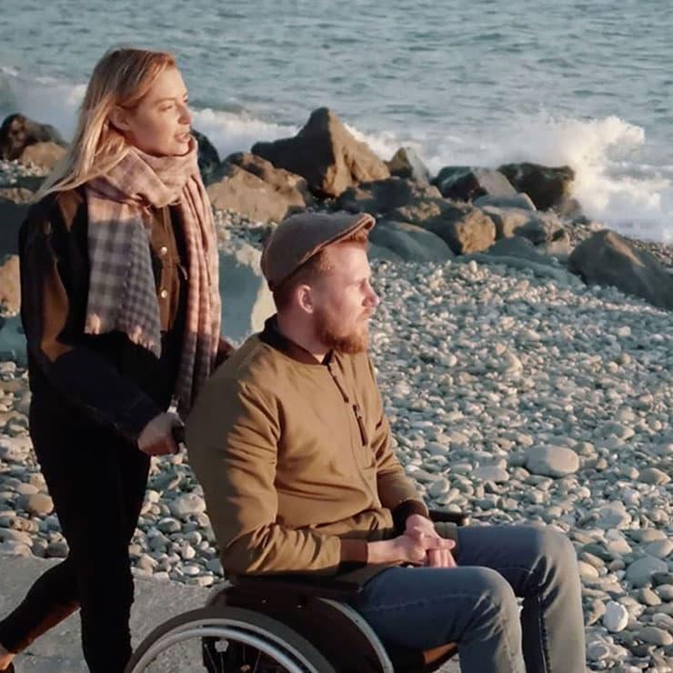 Une femme et un homme en fauteuil roulant se promènent au bord de l'océan