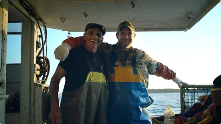 Capture d'écran de la publicité – deux hommes sur un bateau.