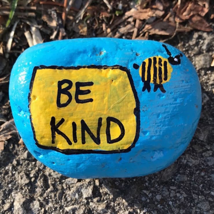 Hand-painted rock that says Be Kind.