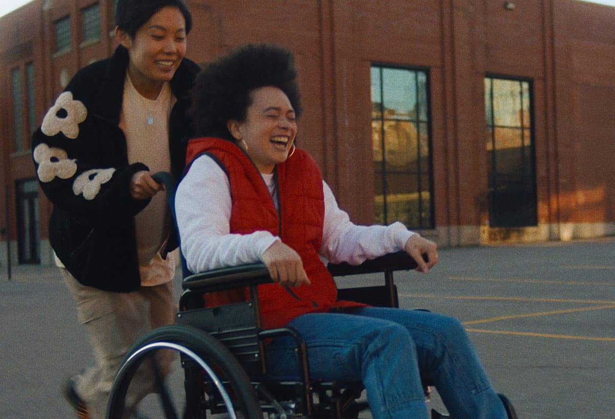Une femme pousse sa partenaire dans un fauteuil roulant.