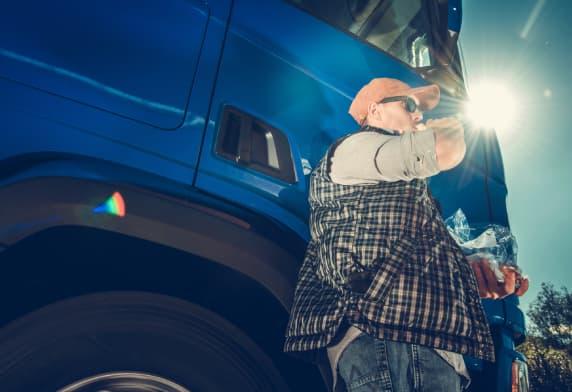 Un homme qui boit de l'eau à l'extérieur de son camion