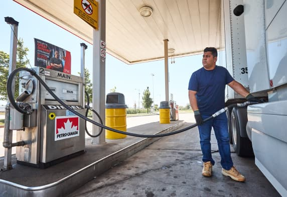 A man pumping gas into a truck