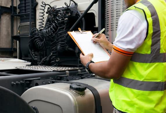 Camionneur écrit sur un presse-papiers avec des chèques réparant un camion