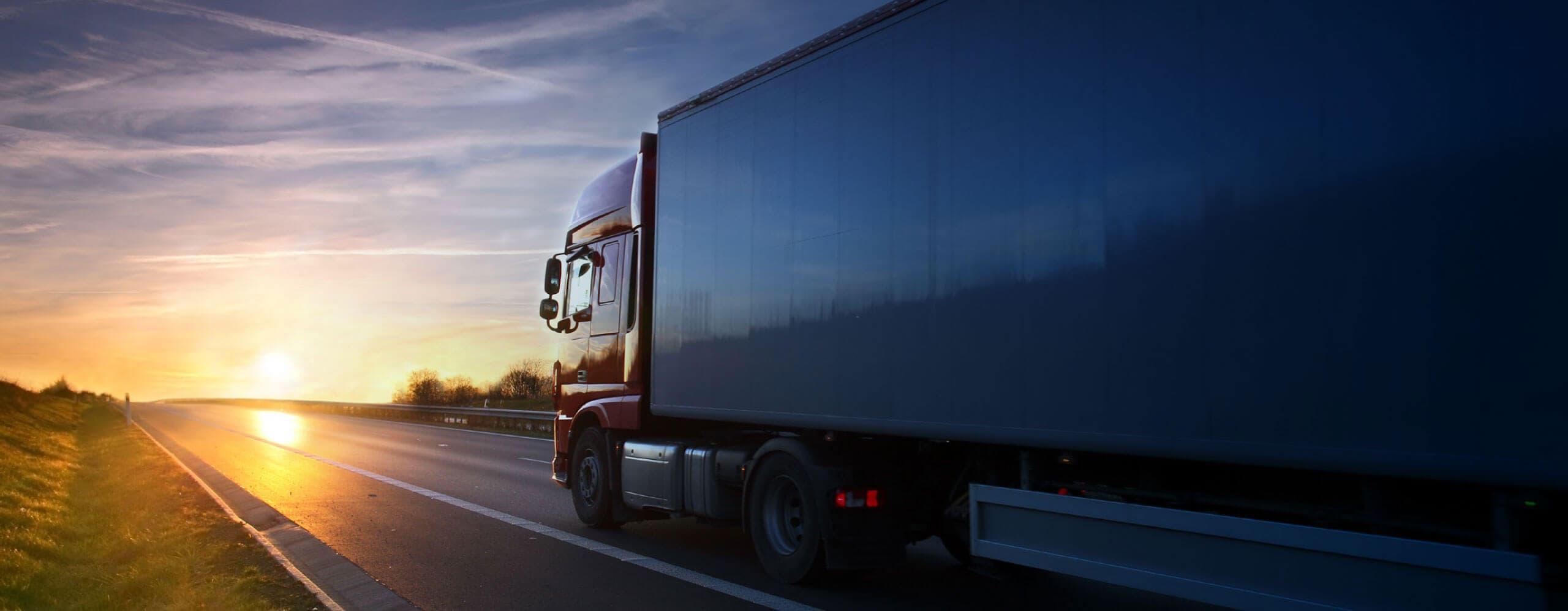 Un camion de transport qui vient vers nous avec le coucher du soleil en arrière-plan.