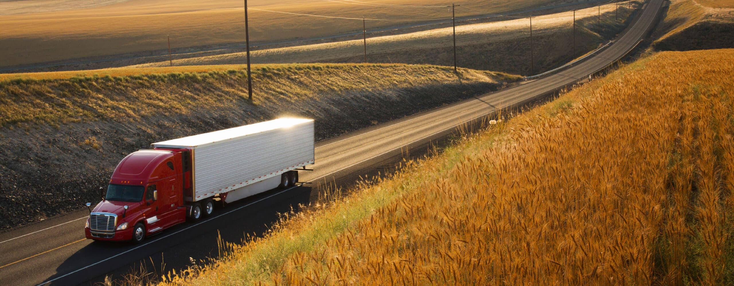 Un camion de transport rouge et blanc qui vient vers nous sur une autoroute à deux voies.