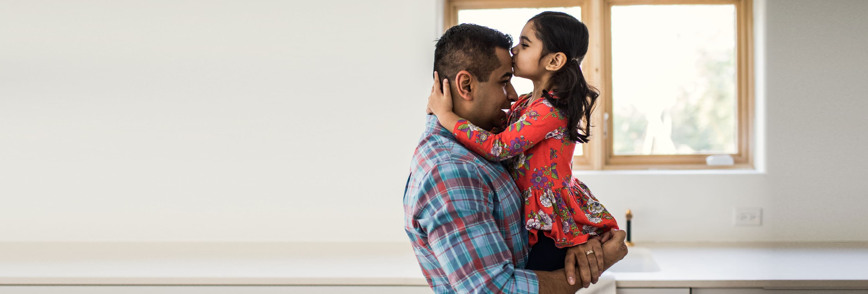 A little girl kissing her fathers forehead.