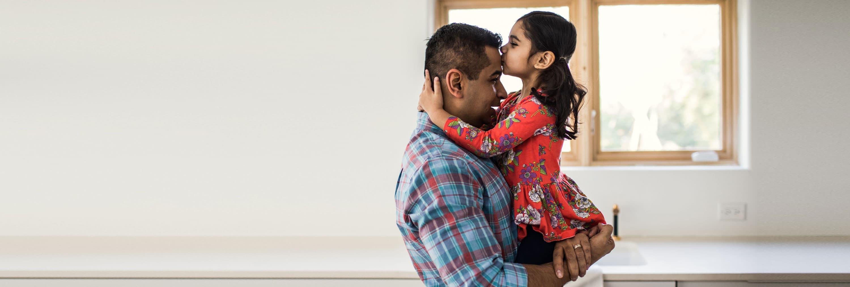 Une petite fille embrassant le front de son père.