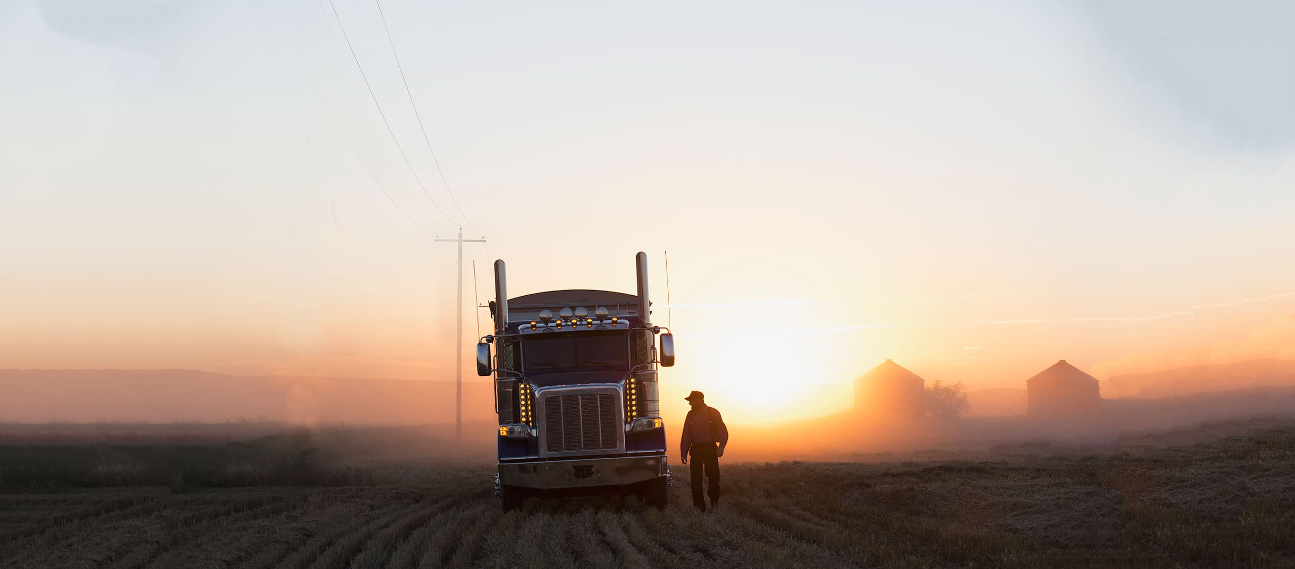 Rig and driver at dusk in a field.