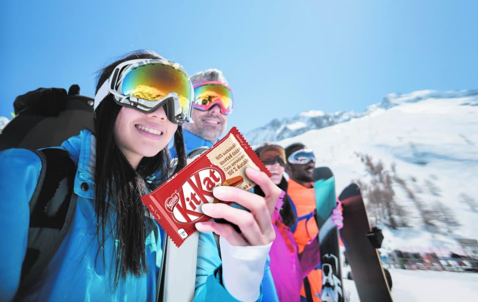 Un groupe de skieurs et une femme tenant une barre de chocolat KitKat.