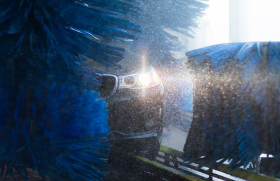 A car peeking through the blue brushes of a Petro-Canada Super Wash