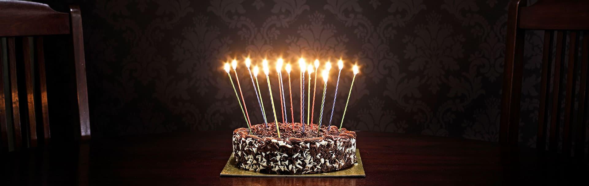 Gâteau d'anniversaire avec chandelles allumées.