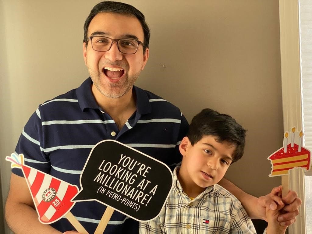 Father and son holding sign that says you're looking at a millionaire (in Petro-Points)