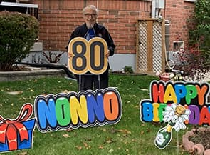Man standing in yard with birthday decorations.