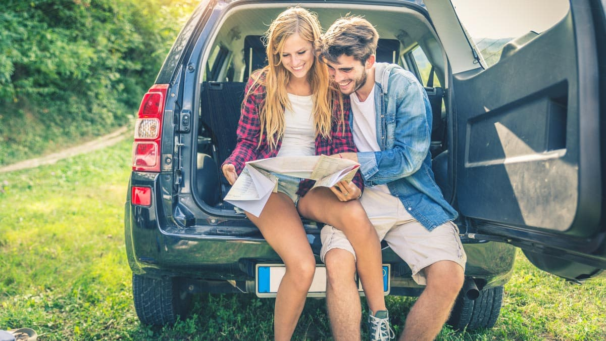 A man and a woman sitting in the back of their SUV and reading a map