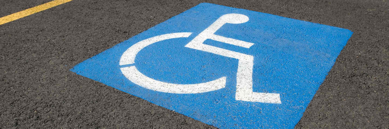 Icône de fauteuil roulant bleue dans un stationnement.
