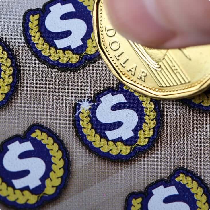 Une pièce de un dollar grattant un billet de loterie.