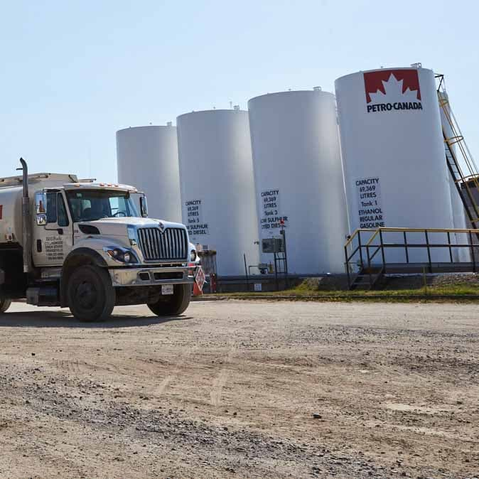 A Petro-Canada truck next to some large fuel tanks