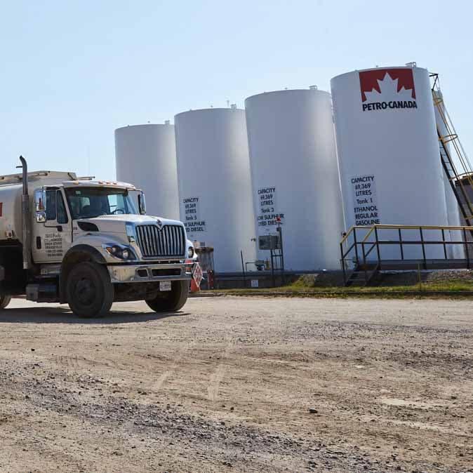 Un camion Petro-Canada à côté de gros réservoirs de carburant.