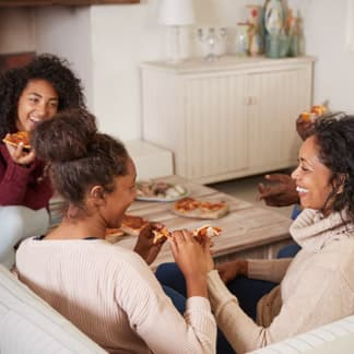 A family sitting in their cozy living room, eating pizza.