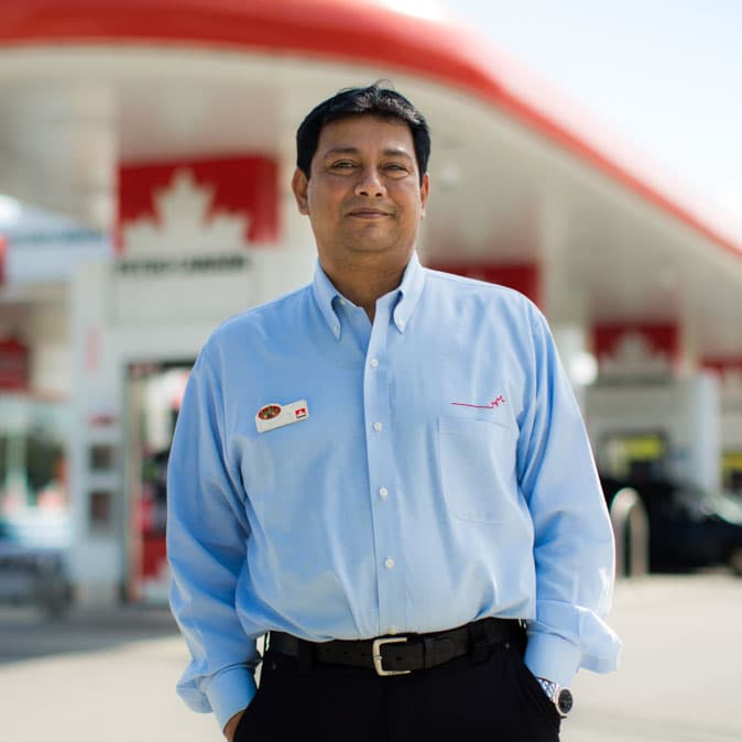 A Petro-Canada employee standing in front of his store.