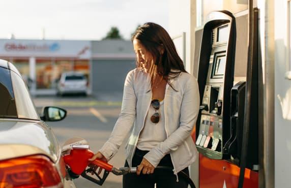 Une femme fait le plein à une station Petro-Canada.