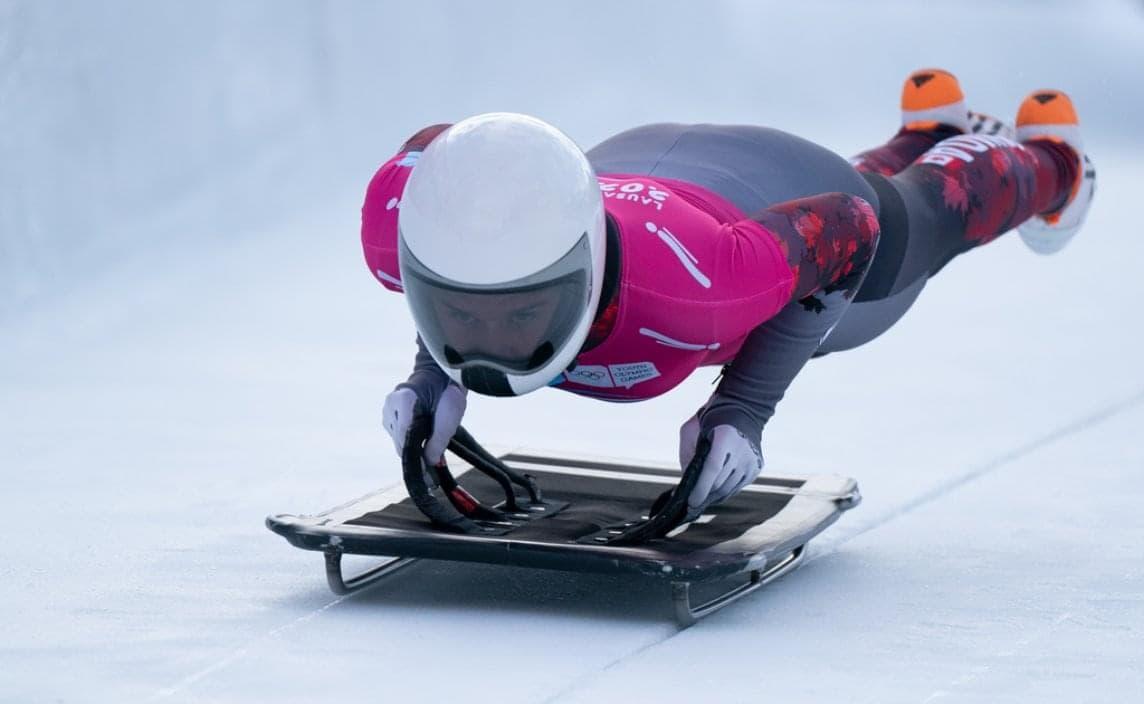 Un patineur de vitesse dans une courbe de la patinoire.