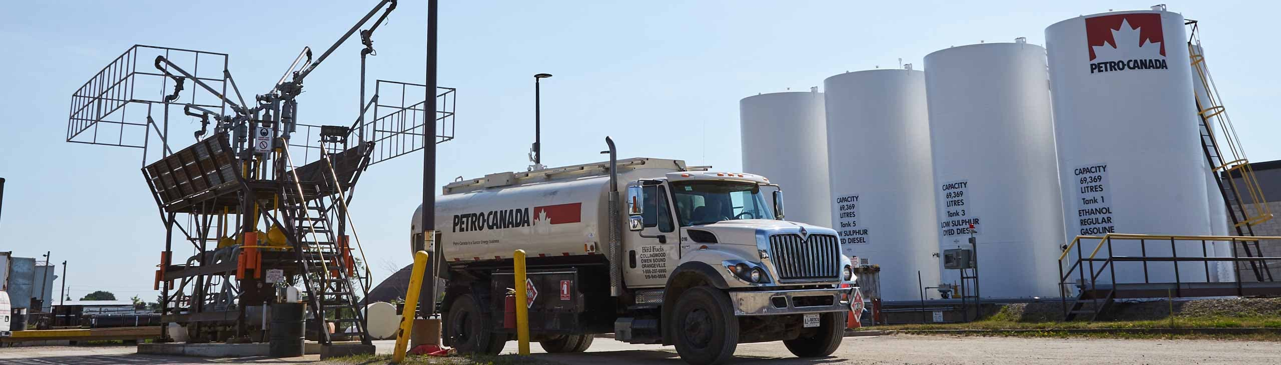 Un camion Petro-Canada devant une rangée de gros réservoirs de carburant.