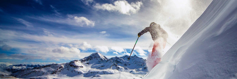 Un skieur que descend une pente abrupte.