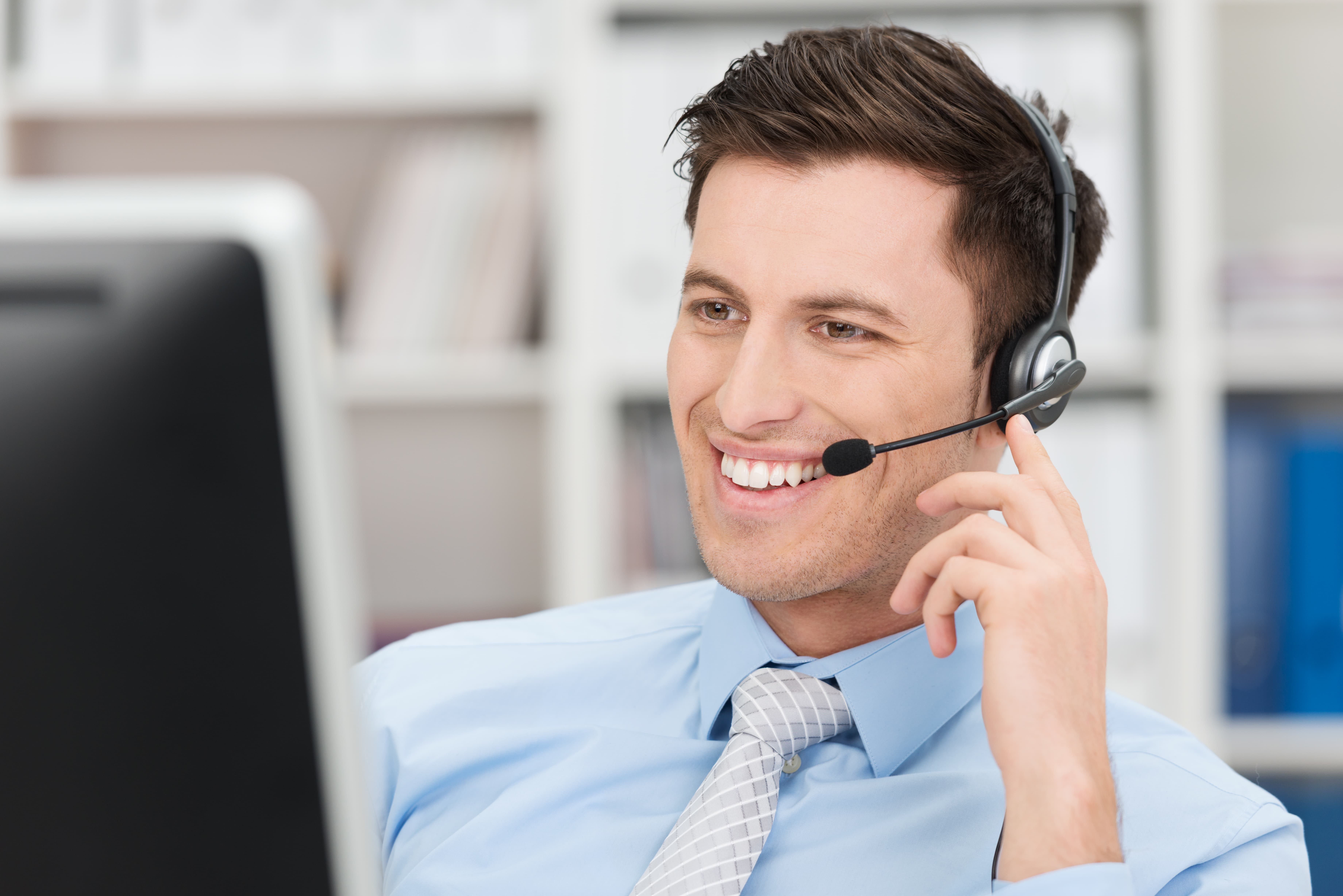 A smiling woman talking on a headset in an office.