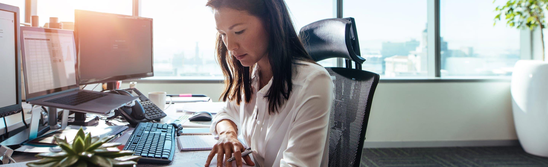 Une femme d'affaires dans un bureau dans un espace ouvert baigné de clarté.