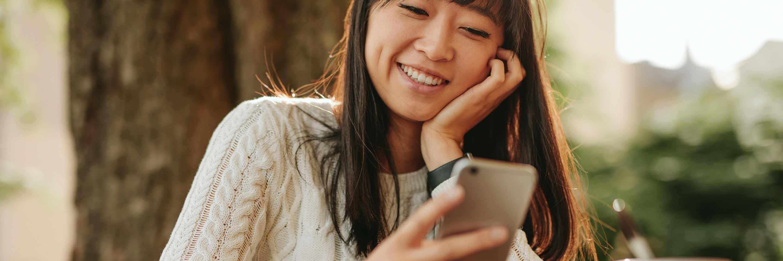 Une femme qui sourit en regardant son téléphone cellulaire.