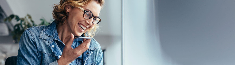 Une femme qui discute sur haut-parleur de son téléphone cellulaire en souriant.