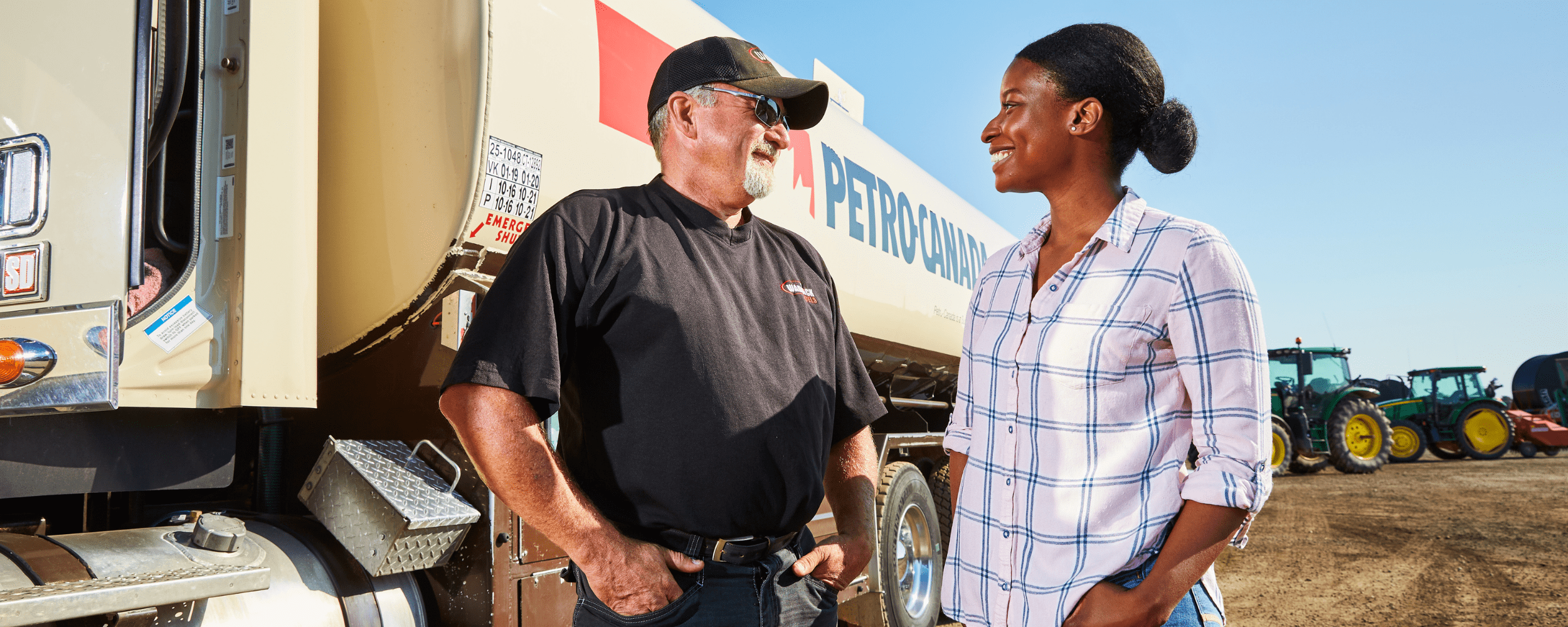 A picture of 2 truck drivers in front of a Petro-Canada truck