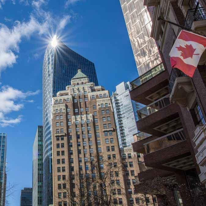 Des édifices au centre-ville et le drapeau du Canada en avant-plan.